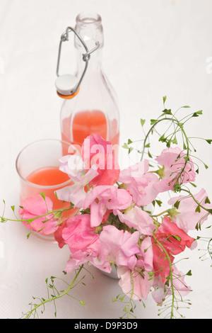 Fiori di colore rosa e una bibita rinfrescante Immagini Stock