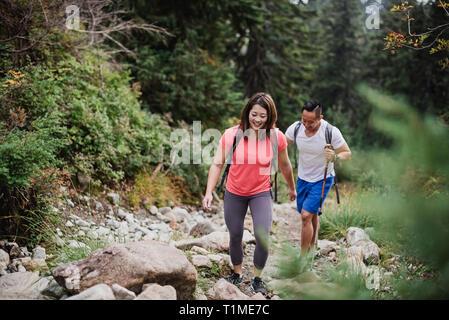 Escursionismo coppia sulle rocce di boschi Immagini Stock