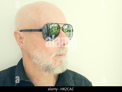 Il vecchio uomo con cool occhiali da sole guardando lontano. Giardino verde riflesse nei bicchieri. Immagini Stock