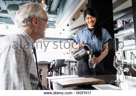 Friendly cameriera versando acqua per senior uomo a pranzo nel ristorante Immagini Stock