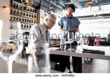 Cameriera prendendo dell'uomo in ordine ristorante Immagini Stock