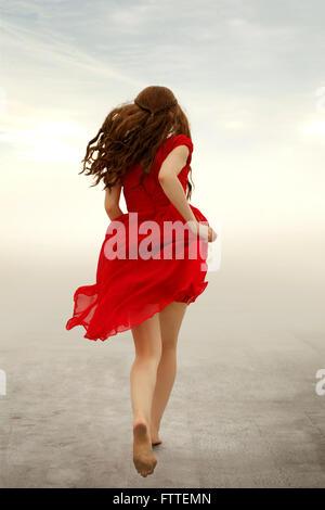 Donna in abito rosso acceso lontano Immagini Stock