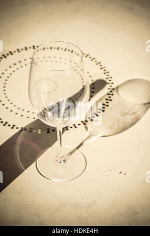 Ombra del bicchiere vuoto e bottiglia di vino sul tavolo. Concetto di immagine di bere e di solitudine. Immagini Stock