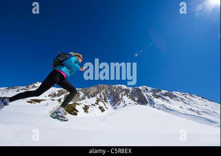 Esecuzione del pareggiatore attraverso le montagne nevose Immagini Stock