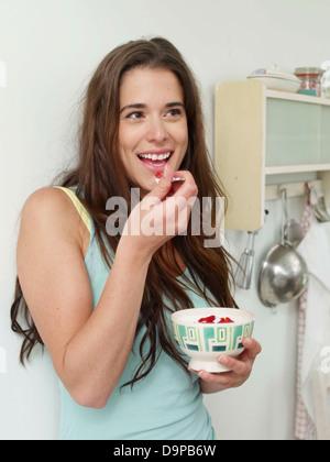Bruna giovane donna di mangiare lo yogurt con fragole Immagini Stock
