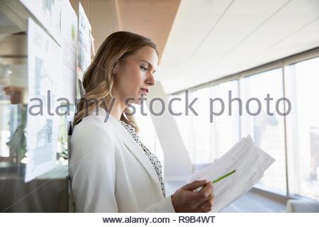 Imprenditrice focalizzato la revisione dei documenti di office Immagini Stock