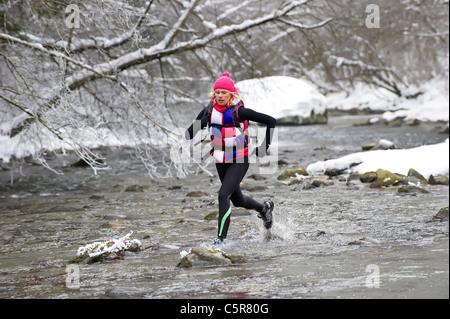 Un pareggiatore attraversando un inverno nevoso fiume. Immagini Stock