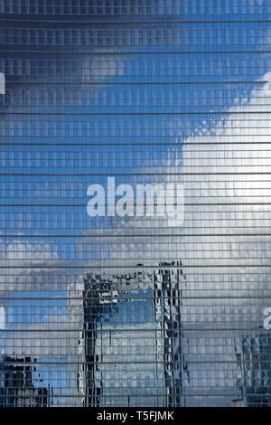 Abstract facciata grattacielo con la riflessione della skyline e le nuvole. Immagini Stock
