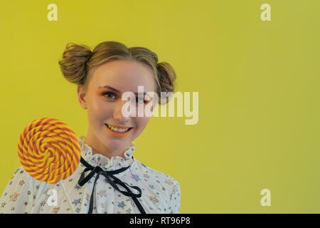 Bella funny girl con brillante trucco tenendo un arancio lecca-lecca. Immagini Stock