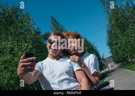 Unione-cerca ragazzo e ragazza africana prendere un selfie su una corsa in bicicletta Immagini Stock