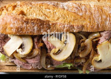 Close up di carni bovine baguette con funghi champignon, insalata verde, cipolla fritti. Laici piana, spazio Immagini Stock