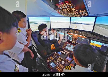 (190717) -- KUNMING, luglio 17, 2019 (Xinhua) -- Gli studenti apprendono da un istruttore (2 R) in una COMAC C919 del simulatore di volo durante un aviation-tema summer camp per la scuola elementare e media gli studenti di Kunming, a sud-ovest della Cina di Provincia di Yunnan, 17 luglio 2019. (Xinhua/Qin Qing) Immagini Stock