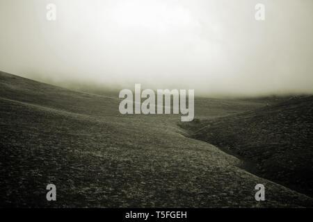 Una nube e la nebbia è espresso sulle praterie di una collina e ridge. Immagini Stock