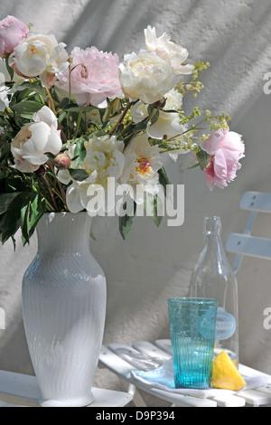 Mazzo di fiori e una bottiglia di acqua minerale, vetro e limone Immagini Stock