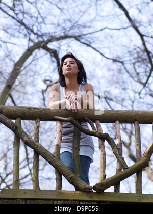 Dai capelli scuri donna in piedi sul ponte di legno Immagini Stock