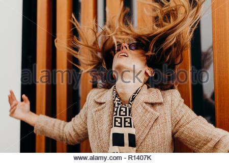 Sezione mediana di una giovane donna nel lanciare i suoi capelli indietro Immagini Stock
