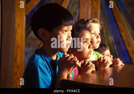 Etnico gruppo misto di giovani bambini cristiani pregare in chiesa il signor © Myrleen Pearson ...Ferguson Cate Immagini Stock