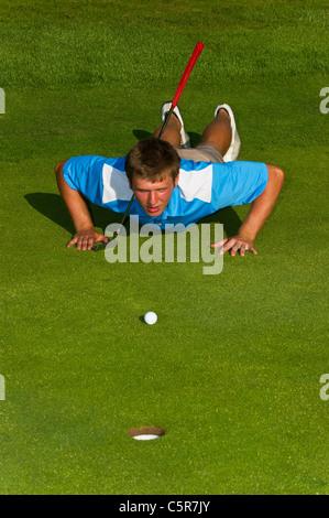 Un golfista fodera fino a mettere sul verde. Immagini Stock