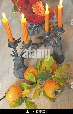 Mazzo di fiori, il candelabro e kakis Immagini Stock