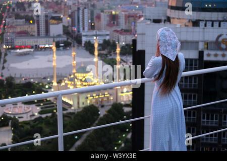 Donna locale guardando da un grattacielo a Grozny City business center si trova a Grozny la capitale della Cecenia ufficialmente la Repubblica cecena nel Nord Caucaso Distretto federale della Russia. Immagini Stock