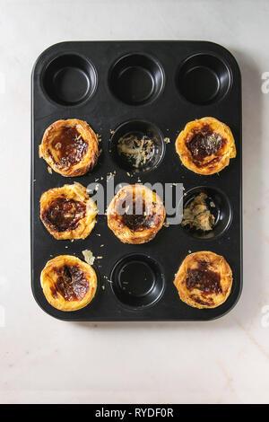Tradizionale portoghese crostata di uova dessert pastello Pasteis de nata in nero vassoio da forno su marmo bianco dello sfondo. Laici piana, spazio Immagini Stock