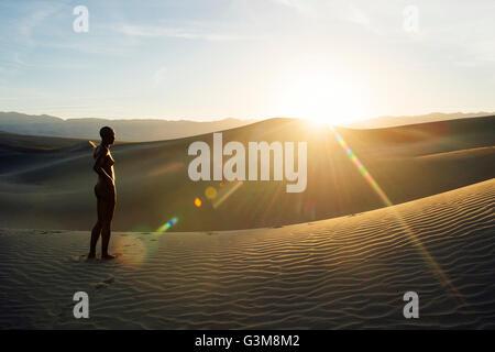 Nudo di donna nel deserto su dune di sabbia che guarda lontano Immagini Stock