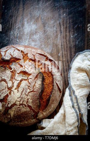 Artigiano del pane di pasta acida con asciugamano da cucina in legno infarinata scheda vintage con spazio di copia Immagini Stock