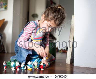 Quattro anni di ragazza che gioca con figure di plastica sul pavimento Immagini Stock