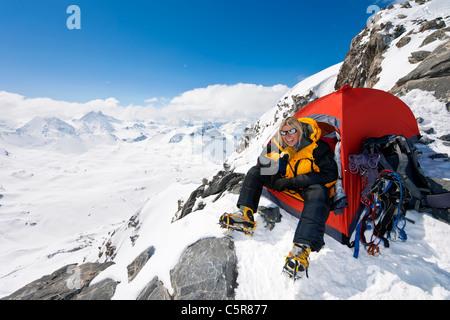 Un felice alpinista seduto alla porta della sua tenda Immagini Stock