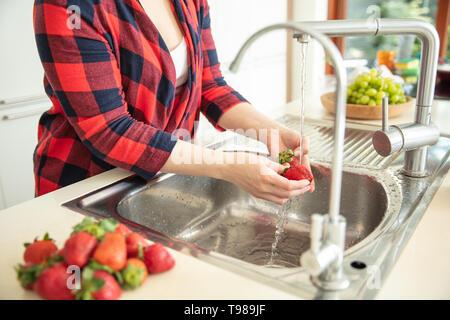 Donna sciacqua le fragole in cucina con uva verde in background e fragole rosso sul primo piano. Immagini Stock