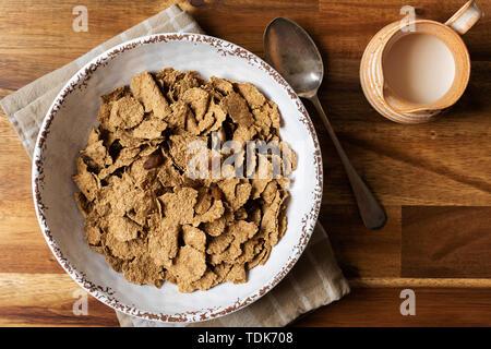 La colazione tazza di crusca di frumento di scaglie e uva sultanina accanto una brocca del latte. Immagini Stock