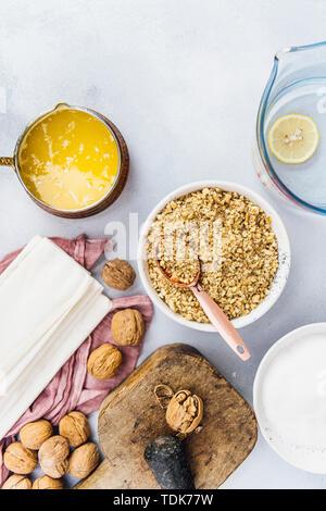 Il baklava turca ingredienti quali noci, burro, fogli di Fillo fotografato su sfondo grigio Immagini Stock