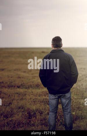 Bel uomo di mezza età a piedi attraverso un territorio rurale della zona costiera Immagini Stock