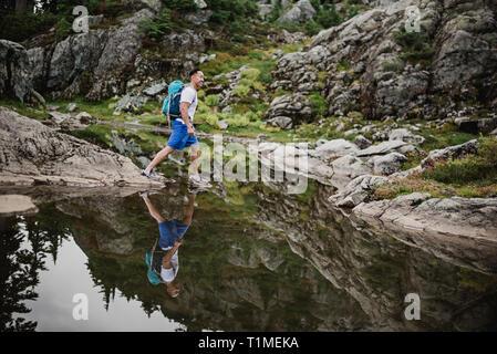 L'uomo escursionismo su acqua, cane montagna, BC, Canada Immagini Stock