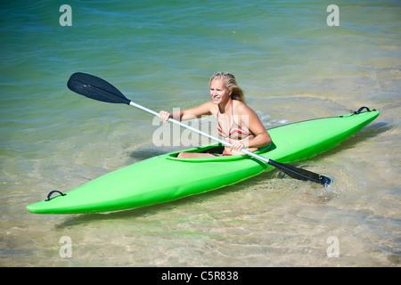 Una giovane donna sguazzare un kayak. Immagini Stock