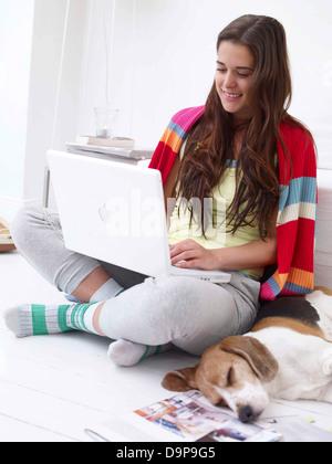 Giovane donna con il cane di casa utilizzando laptop Immagini Stock