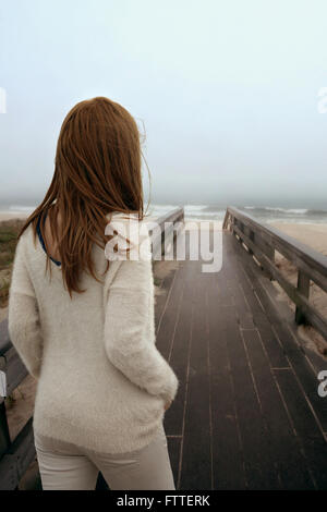 Donna che cammina sulla passerella di legno a beach Immagini Stock