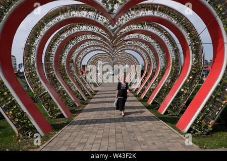 Donna locale a piedi attraverso una a forma di cuore in tunnel Tsvetochny o fiore parco nel centro di Grozny capitale della Cecenia ufficialmente la Repubblica cecena nel Nord Caucaso Distretto federale della Russia. Immagini Stock