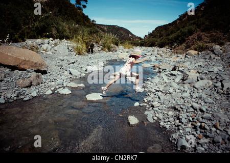 Ragazza salta su pietre miliari attraverso stream, Nuova Zelanda. Immagini Stock