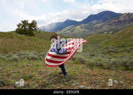 Ragazzo holding bandiera americana in colline Immagini Stock