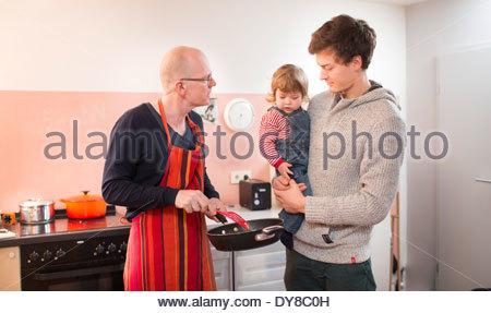 Nonno preparare il cibo per il suo figlio e nipote Immagini Stock