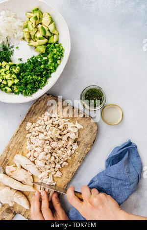 Donna in camicia per tritare i petti di pollo su una tavola di legno per fare un avocado insalata di pollo ricetta Immagini Stock