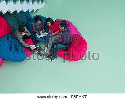 La gente di affari in bean bag sedie guardando al laptop Immagini Stock