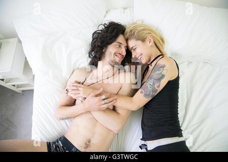 Un giovane tatuato giovane cuddling su un letto. Immagini Stock