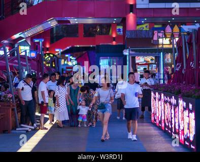 Urumqi, della Cina di Xinjiang Uygur Regione autonoma. 14 Luglio, 2019. La gente a fare una passeggiata in un centro commerciale per lo shopping in Urumqi, a nord-ovest della Cina di Xinjiang Uygur Regione autonoma, luglio 14, 2019. Notte-economia di tempo è stato il prelievo in Urumqi a partire dal mese di luglio. Le persone si divertono a raffreddare le notti estive da shopping e degustazione del cibo. Credito: Zhao Ge/Xinhua/Alamy Live News Immagini Stock