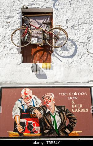Irlanda, Co Louth, Carlingford, vecchia banchina Lane, noleggio bici Bicicletta sospesa sopra ma Baker's Bar pubblicità segno Immagini Stock