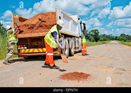 I lavoratori stradali autostrada di riempimento di buche in Manyama, Zambia. Immagini Stock