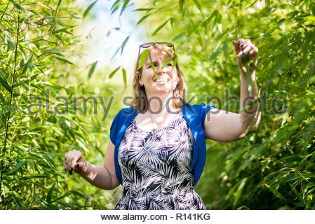 Vista frontale di un sorridente giovane donna in piedi contro piante Immagini Stock