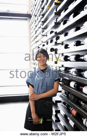 Ritratto sorridente e fiducioso sommelier femmina permanente al rack di vino nel ristorante Immagini Stock