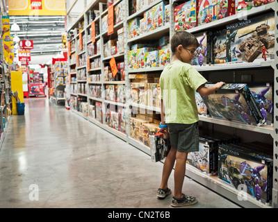 Ragazzo decide sul giocattolo per comprare con il suo pocket money in un negozio di giocattoli. Immagini Stock